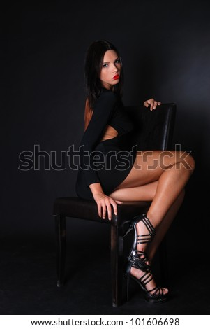 Full body of a beautiful woman with sexy body and sexy poses wearing black dress on black background