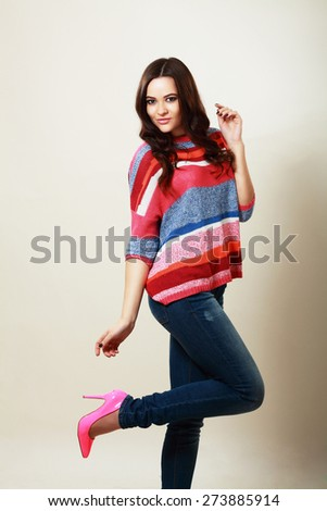 Full body of a casual young woman pointing to copyspace - stock photo