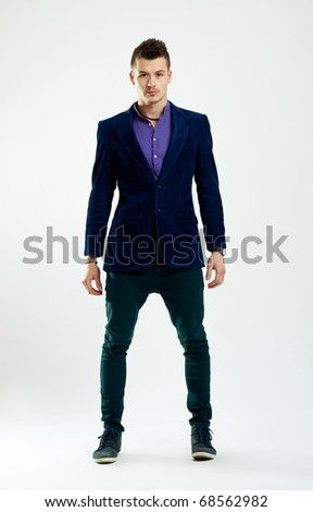 Full body of a handsome young brunette man wearing  shirt and dark jacket and jeans - stock photo