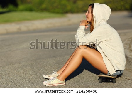 Full body of a profile of a pensive teenager girl sitting on a skate in the street looking away              - stock photo