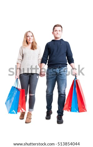 Full body of happy handsome couple holding bunch of shopping bags holding hands and smiling isolated on white background
