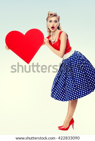 Full body of woman holding heart symbol, dressed in pin-up style dress with polka dot. Caucasian blond model posing in retro fashion and vintage concept studio shoot. - stock photo