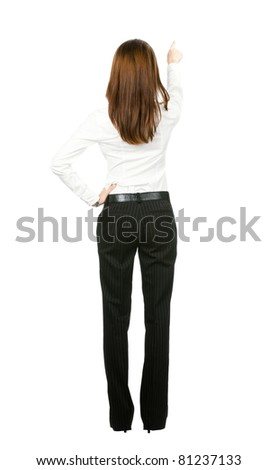 Full body of young business woman pointing at something in her back, isolated on white background