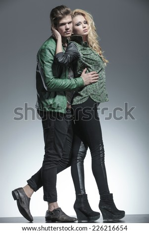 Full body picture of a beautiful fashion woman holding her lover while he is holding her. Both looking at the camera. - stock photo