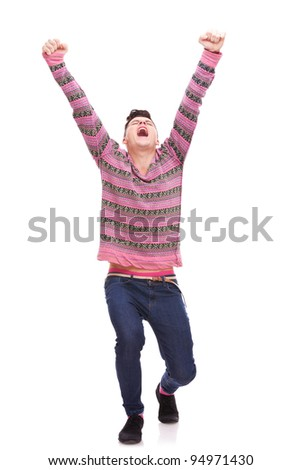 full body picture of  a casual man looking very happy with his arms up against white background . young casual man gesturing success and being very excited - stock photo