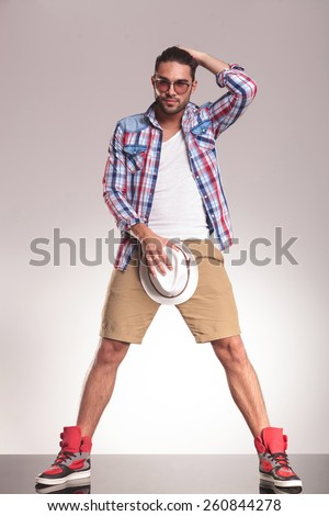 Full body picture of a casual youn man standing on studio backgroud, holding his hat to his crotch while the other one is in his hair. - stock photo