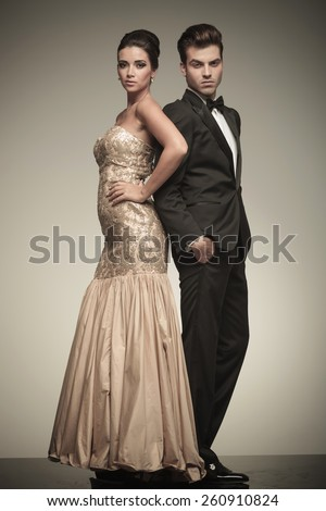 Full body picture of a elegant couple posing on studio background. He is holding both hands in his pocket while she is looking at the camera. - stock photo