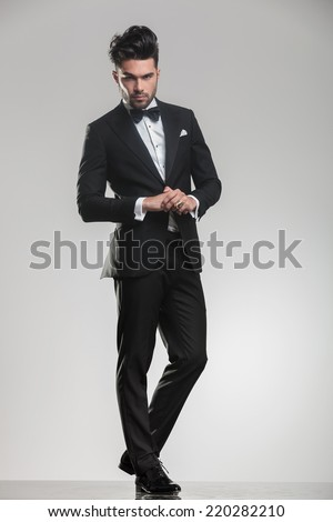 Full body picture of a elegant young man wearing a tudexo looking at the camera while holding his hands,