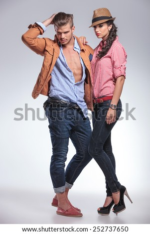 Full body picture of a fashion couple posing on studio background while looking down. - stock photo