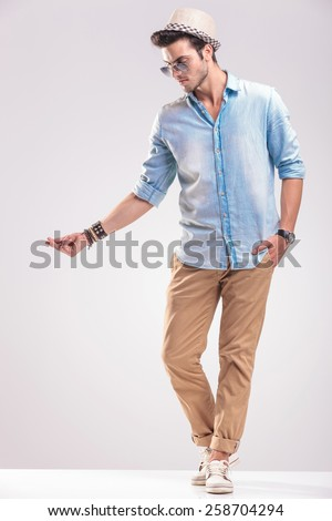 Full body picture of a fashion man looking down while snappig his fingers, on grey studio background. - stock photo