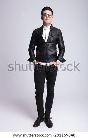 Full body picture of a handsome fashion man standing on studio background with his hands in pockets. - stock photo