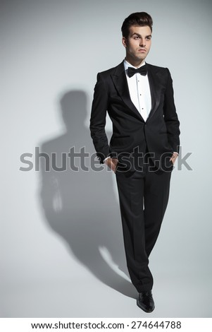 Full body picture of a handsome young business man walking with his hand in pockets on studio background. - stock photo