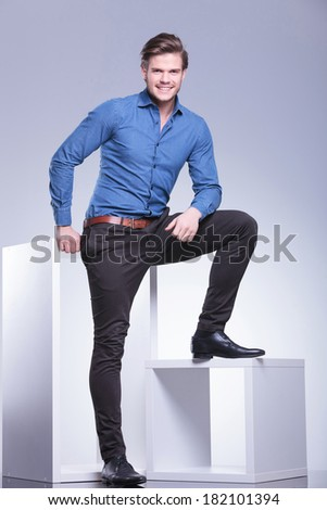 full body picture of a relaxed smiling casual man standing with leg on a cube - stock photo