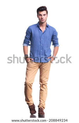 full body picture of a young casual man with hands in his pockets on white background - stock photo