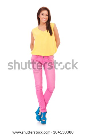 full body picture of a young casual woman standing with her hands at her back over white background - stock photo