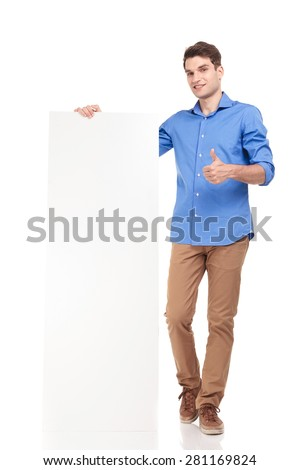 Full body picture of a young fashion man holding a empty board while showing the thumbs up gesture. - stock photo