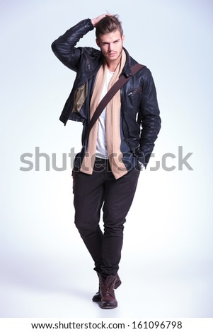 full body picture of a young fashion model passing his hand through his hair and smiling to the camera - stock photo