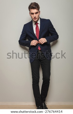 Full body picture of a young handsome business man opening his jacket. - stock photo