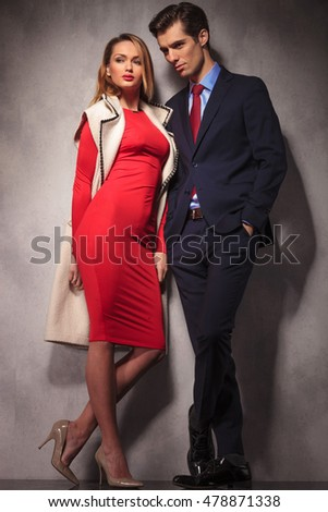 full body picture of an elegant couple looking to side standing against wall, in studio