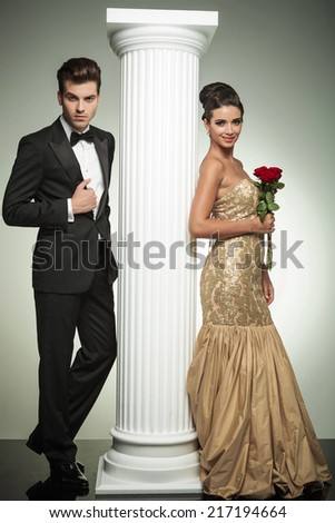 full body picture of an elegant couple near column, woman holding roses in her hand - stock photo