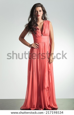 full body picture of an elegant woman in red dress standing with hand on hip on grey background - stock photo