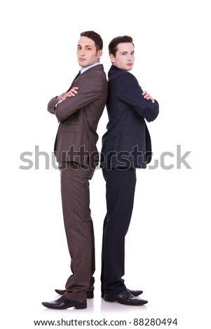 full body picture of two serious business men standing back to back over white background