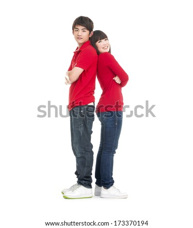 Full body playful young couple standing back to back - stock photo