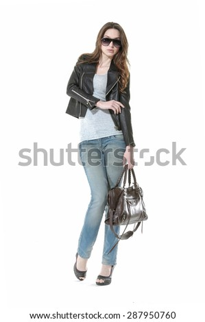 Full body Portrait of a beautiful young woman in jeans with sunglasses posing - stock photo