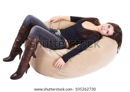 Full-body portrait of a beautiful young woman with long brown hair, wearing boots, jeans, lying on soft stool - isolated on white - stock photo