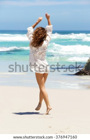 Full body portrait of a carefree young woman in summer dress walking to water on beach - stock photo