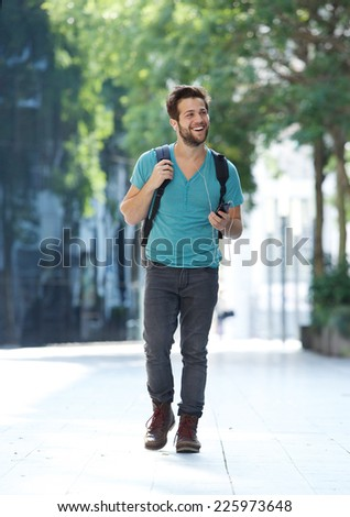 Full body portrait of a cheerful young man walking with mobile phone and bag - stock photo
