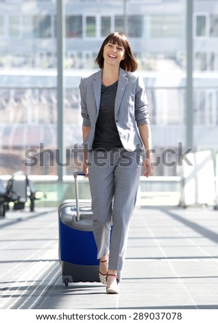 Full body portrait of a happy business woman walking with suitcase at airport - stock photo