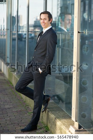 Full body portrait of a happy businessman standing outdoors - stock photo