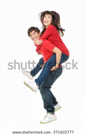 Full body portrait of a happy young couple hugging in studio