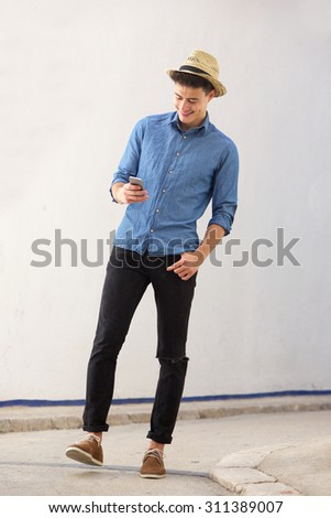 Full body portrait of a smiling young handsome man walking and looking at mobile phone