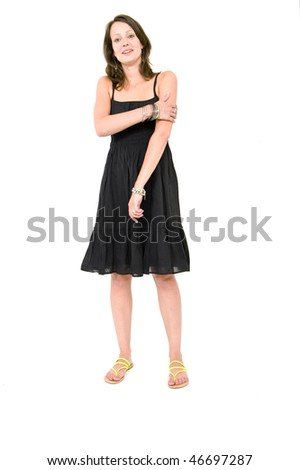 Full body portrait of a young brunette woman in a black summer dress, holding her arm being self aware - stock photo