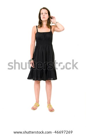 Full body portrait of a young brunette woman in a black summer dress, lifting her hear and listening - stock photo