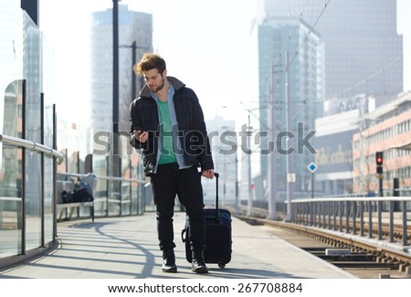 Full body portrait of a young man traveling with bag and mobile phone - stock photo