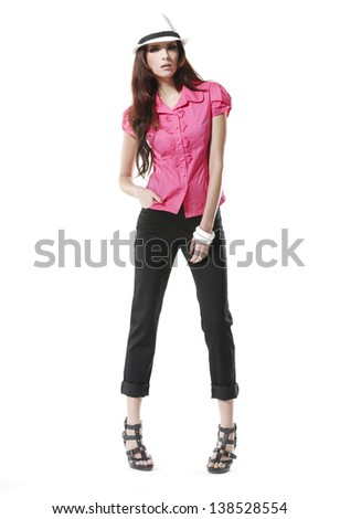Full body Portrait of an attractive young woman posing wearing a hat at studio - stock photo