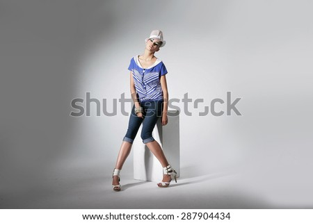 Full body Portrait of beautiful casual young fashion sitting cube model shot in studio - stock photo