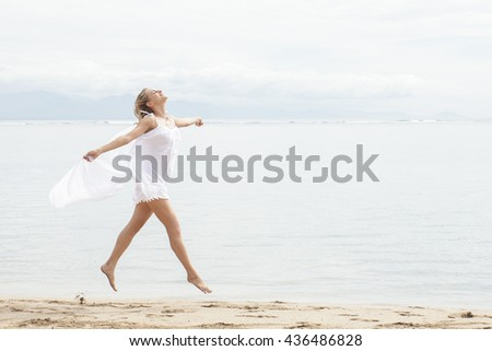 full body portrait of beautiful woman with scarf feeling free on the beach with copy space - stock photo