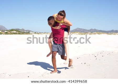 Full body portrait of carefree couple enjoying on the beach, man carrying his girlfriend on his back and walking. - stock photo