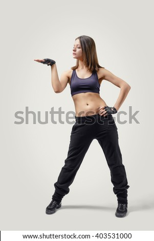 Full body portrait of girl dancer looking at her raised right hand palm up. Front view. - stock photo