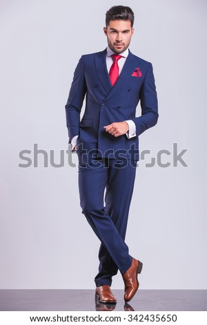 full body portrait of handsome business man posing standing legs crossed with hand in pocket - stock photo