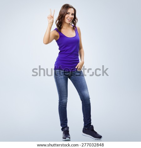 Full body portrait of happy smiling beautiful young woman showing two fingers or victory gesture, against grey background, with blank copyspace area for slogan or text - stock photo