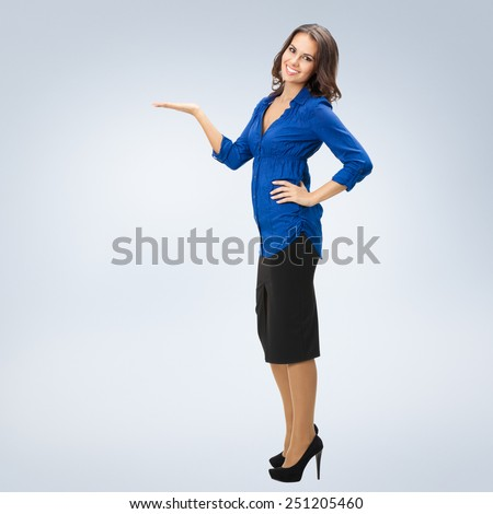 Full body portrait of happy smiling young businesswoman showing something or copyspase for product or sign text - stock photo