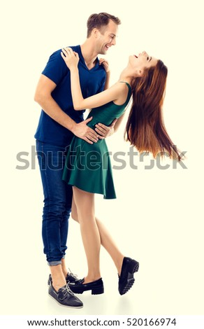 Full body portrait of hugging or dancing couple, looking at each other, with smile. Caucasian models in love, relationship, dating, flirting, lovers, romantic studio concept.