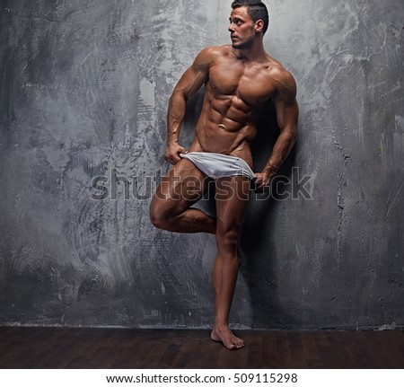 Full body portrait of muscular suntanned male model in white panties posing near grey wall in a studio.