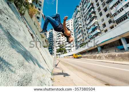 Full body portrait of parkour man jumping high in the street performing a backflip. - stock photo