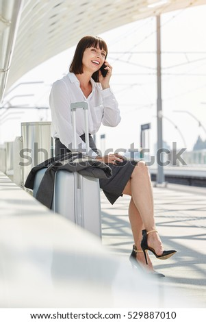 Full body portrait of smiling professional woman waiting at platform talking on phone